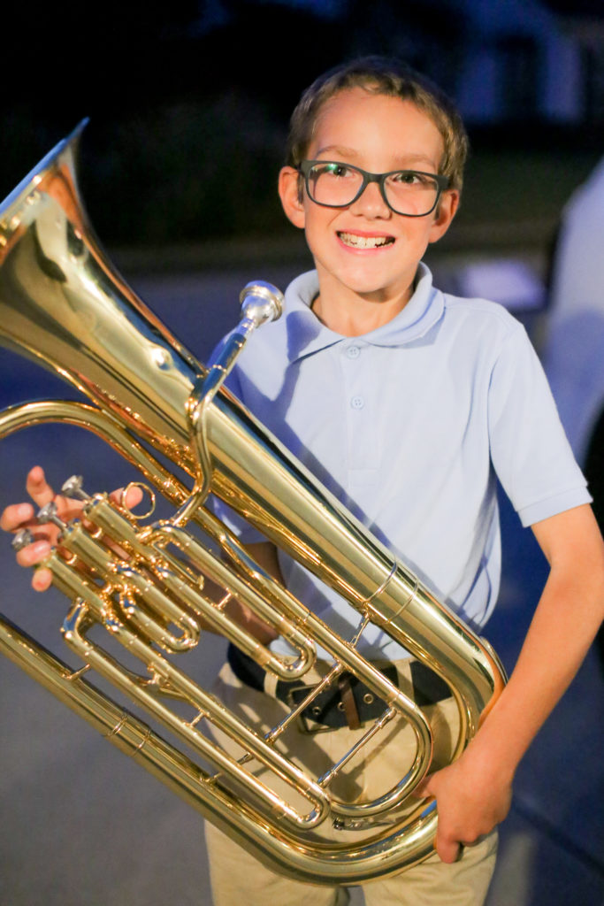 Fourth-grader Miguel Billings, 10, of Collinsville flashes a smile for a portrait with his baritone Wednesday, Nov. 2, 2016 outside of his Collinsville home. Billings has been playing the baritone for hours on end to raise money in order to build a home for a Haitian family. (Photograph by Brian Munoz / The Collinsville Chronicle)